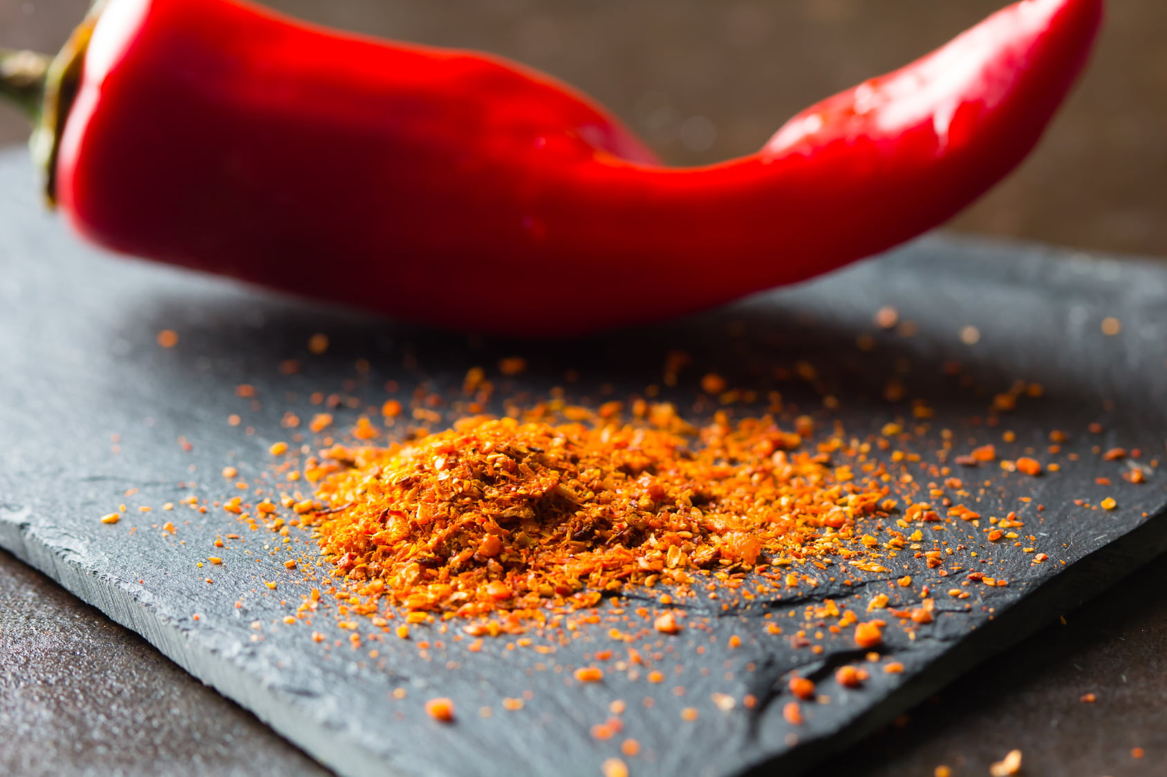 Closeup of dry ground chile on stone board with fresh red  chili on background