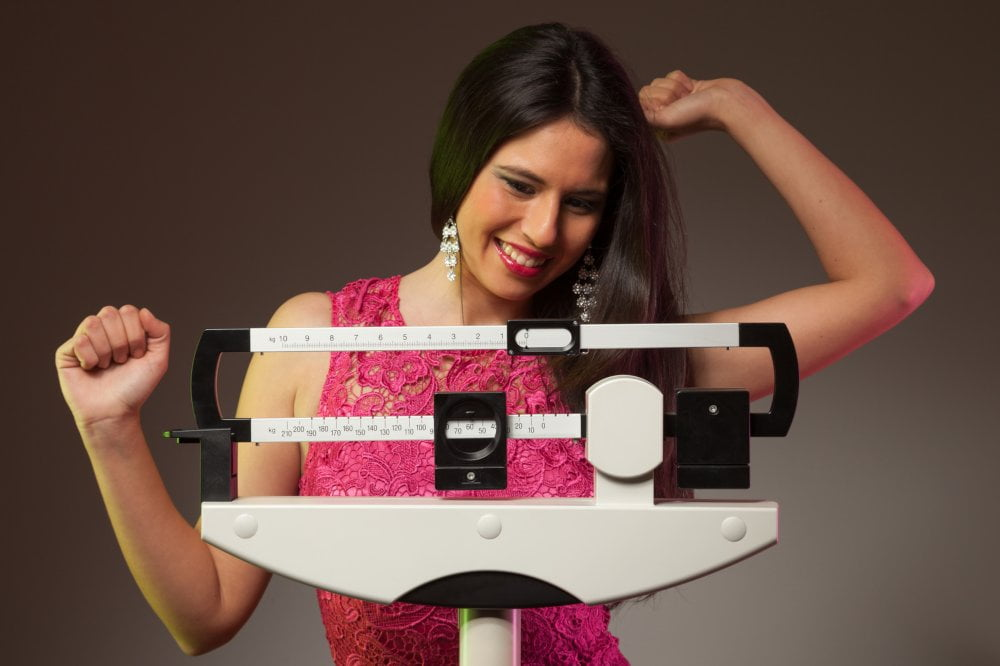 Happy woman on the scale